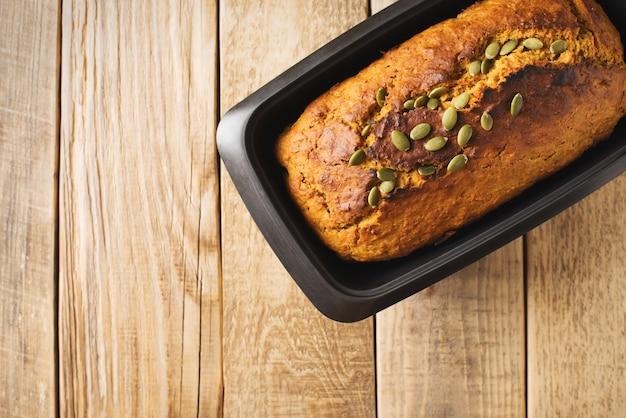 Abóbora caseira com bolo de sementes em fundo de madeira. dia de ação de graças e tema de outono