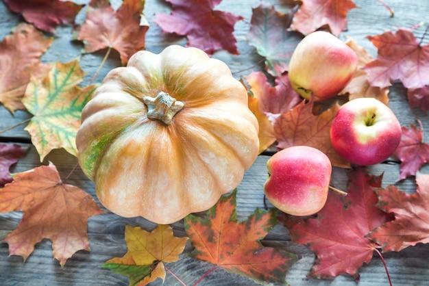 Abóbora com maçãs no fundo de madeira