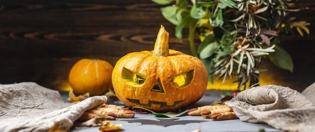 Abóbora com rosto e luz por dentro e dedos de biscoitos de uma bruxa para festa de halloween