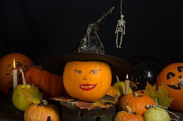 Abóbora com rosto pintado em chapéu de bruxa com velas e outras abóboras