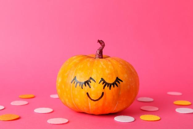 Abóbora com sorriso no espaço decorativo rosa, para texto