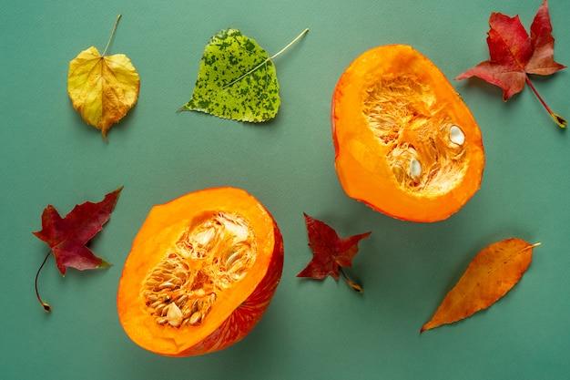 Abóbora cortada ao meio com folhas de outono sobre fundo verde