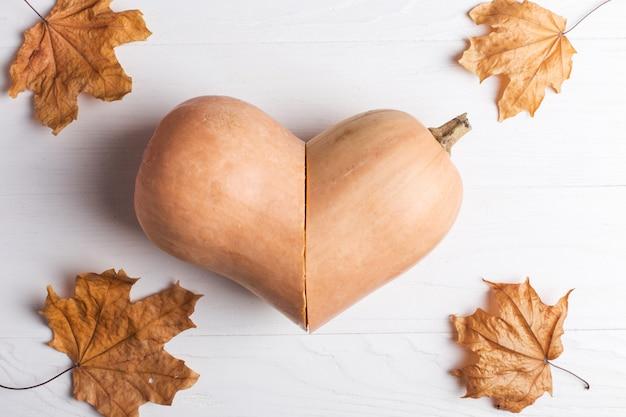 Abóbora cortada em forma de coração e folhas amarelas, outono e colheita.