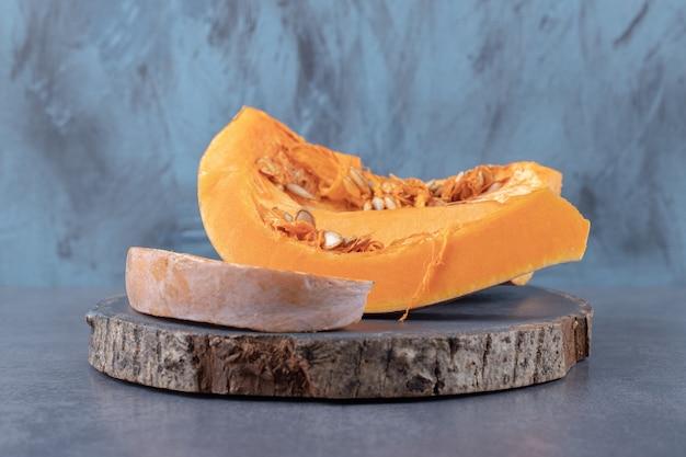 Abóbora cortada em pedaços, num tabuleiro, na superfície do mármore.