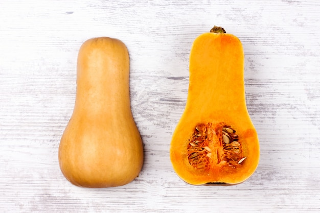 Abóbora cuted em uma mesa branca. abóbora laranja em forma de pêra doce