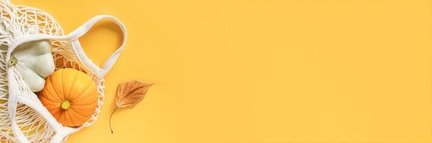 Abóbora de cabaças de vegetais frescos de colheita, abóbora pattypan no saco de malha ecológico de compras, folhas de outono em fundo amarelo. colheita de vegetais orgânicos do conceito. banner de modelo de layout plano de vista superior.