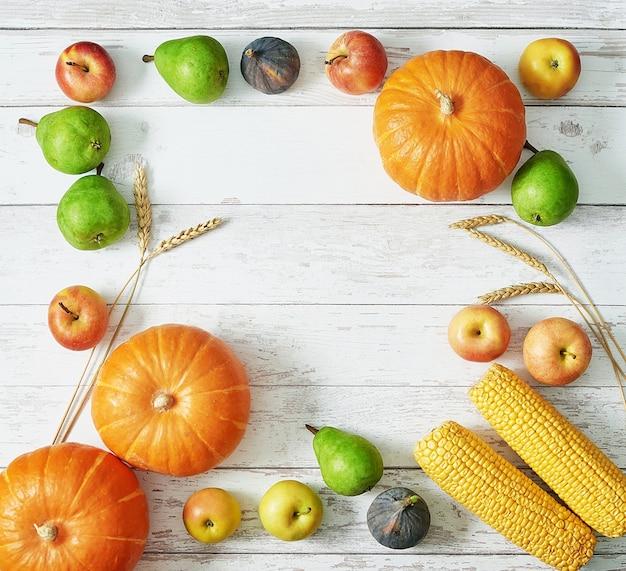 Abóbora de colheita de outono. frutas e vegetais da colheita do outono. abóboras, maçãs, peras, milho na mesa. mesa de ação de graças. dia das bruxas ou outonal sazonal. cartão de felicitações. cozinha de outono.