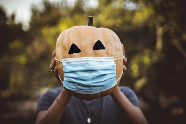 Abóbora de halloween 2020 com uma máscara devido ao covid 19