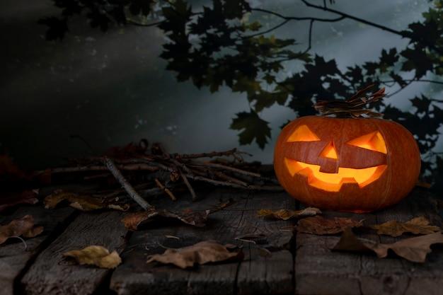 Abóbora de halloween brilhando em uma floresta mística à noite. fundo de horror jack o lantern. projeto de dia das bruxas com copyspace.