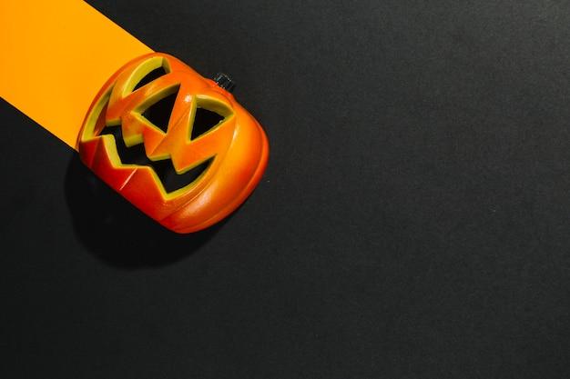Abóbora de halloween colocado na folha de papel laranja