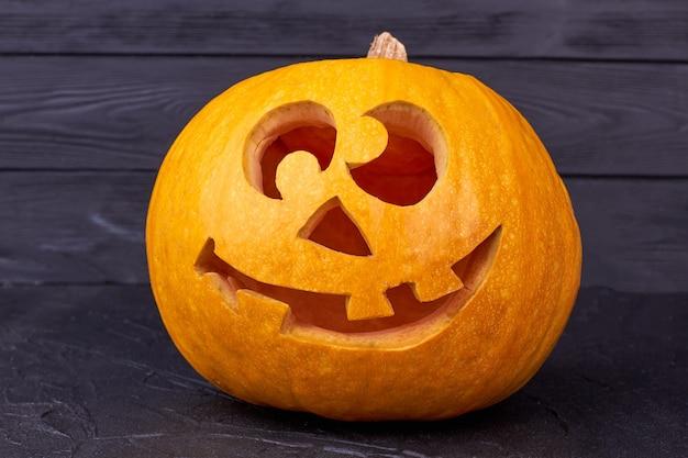 Abóbora de halloween com cara engraçada em fundo preto.