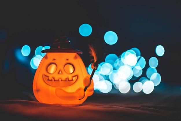 Abóbora de halloween com chapéu de bruxa e fundo de bokeh