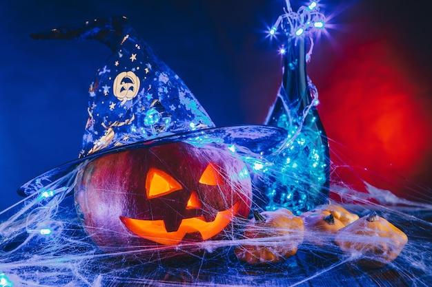 Abóbora de halloween com chapéu em uma teia de aranha com doces e iluminação escura. conceito de doçura ou travessura em fundo azul e vermelho