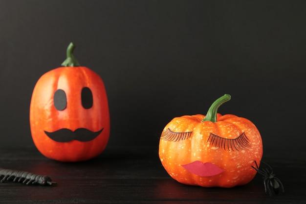 Abóbora de halloween com maquiagem em fundo preto. fundo mínimo do conceito de temporada de férias. homem e mulher