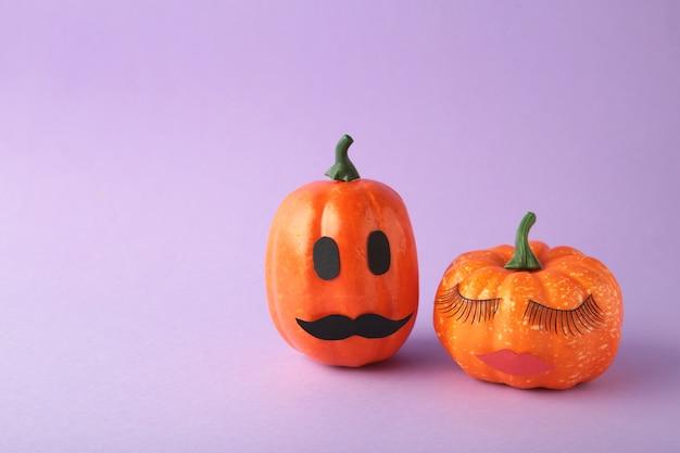Abóbora de halloween com maquiagem. fundo mínimo do conceito de temporada de férias. homem e mulher