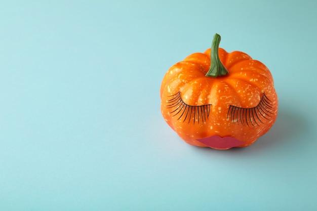 Abóbora de halloween com maquiagem. fundo mínimo do conceito de temporada de férias. vista do topo