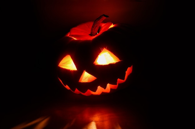 Abóbora de halloween com rosto brilhante esculpido no escuro.