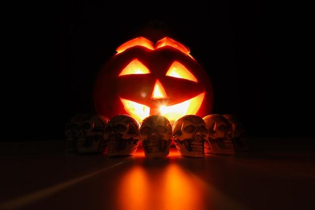 Abóbora de halloween com rosto brilhante esculpido rodeado por pequenos crânios no escuro.