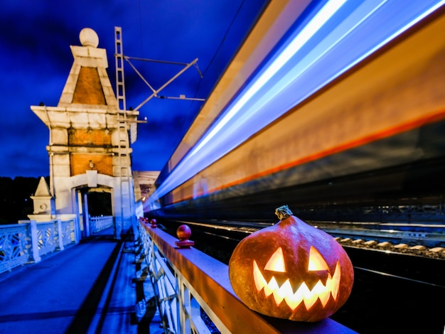 Abóbora de halloween com uma careta brilhante à noite na ponte ferroviária.