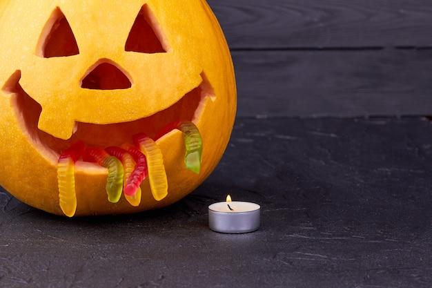 Abóbora de halloween com vela em fundo escuro.