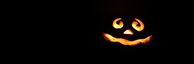 Abóbora de halloween de rosto sorridente brilhante, suporte de vela, isolado em fundo preto escuro à noite. espaço para texto.