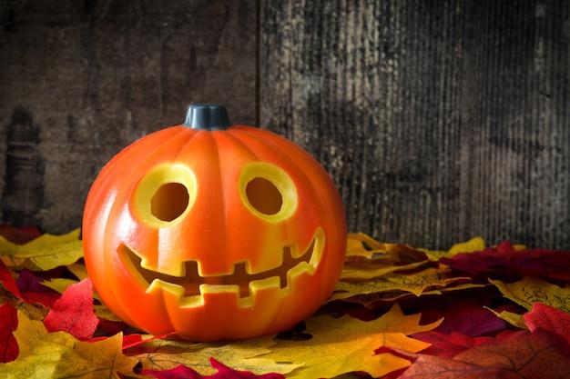 Abóbora de halloween e folhas de outono em fundo de madeira