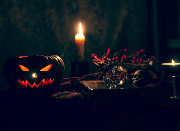 Abóbora de halloween em um fundo preto místico. velas acesas, um símbolo das férias de outono.