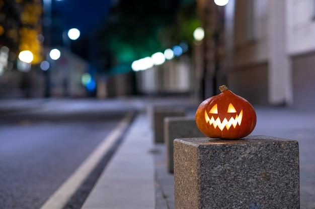 Abóbora de halloween em uma rua deserta da cidade à noite, luzes coloridas borradas da cidade e edifícios antigos ...