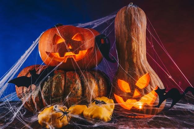 Abóbora de halloween em uma teia de aranha com doces e iluminação escura. conceito de doçura ou travessura em fundo azul e vermelho