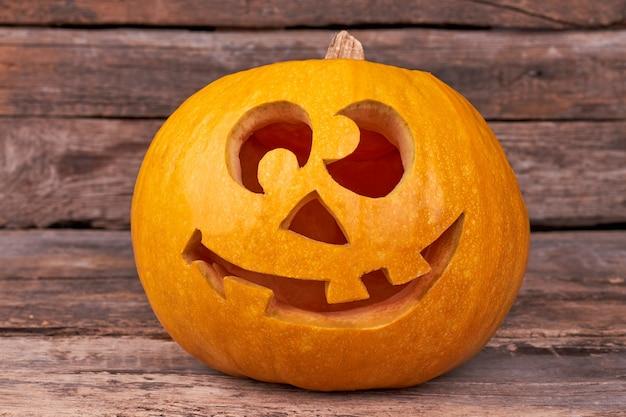 Abóbora de halloween engraçada em fundo de madeira.