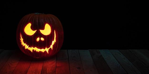 Abóbora de halloween esculpida com vela dentro em pranchas de madeira.