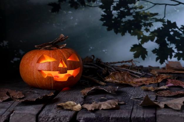 Abóbora de halloween jack o lantern brilhando em uma floresta mística à noite.