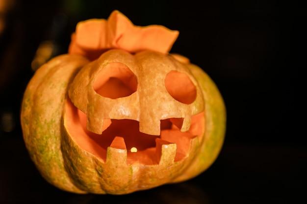 Abóbora de halloween laranja com cara engraçada sobre o fundo escuro
