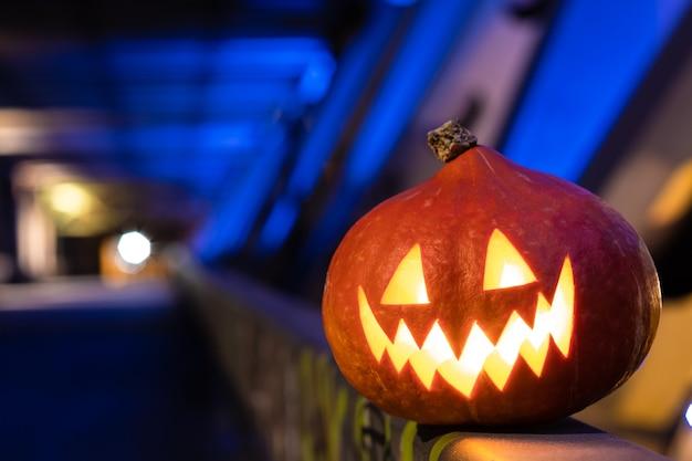 Abóbora de halloween no escuro em um fundo azul industrial abstrato com luzes coloridas embaçadas