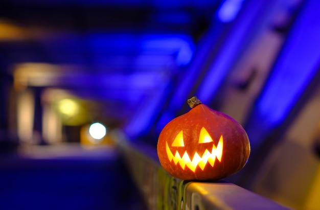 Abóbora de halloween no escuro sobre um fundo azul industrial abstrato.