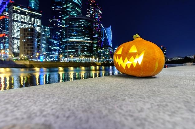 Abóbora de halloween no fundo dos arranha-céus da cidade de moscou, à noite, edifícios de vários andares e azul.