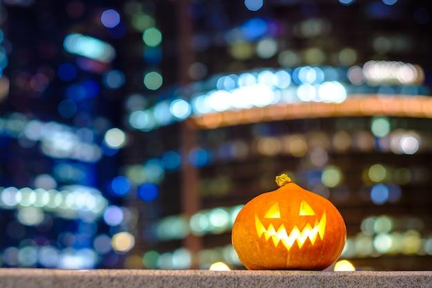 Abóbora de halloween nos edifícios da cidade à noite e arranha-céus luzes coloridas borradas da iluminação da cidade decoração da cidade à noite com um espaço de cópia do tema festivo de halloween