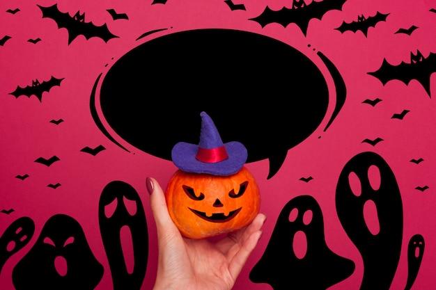 Abóbora de halloween segurar em uma mão feminina em um chapéu de bruxa azul com balão preto
