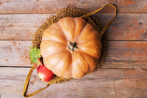 Abóbora de outono em uma sacola ecológica de algodão de malha com maçãs, cogumelos cardoncelli, nozes, folhas em placas de madeira velhas. compras no outono, colheita, zero desperdício