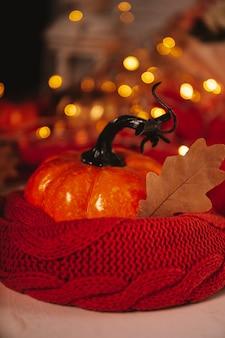 Abóbora de outono laranja em um lenço com bela foto vertical bokeh com espaço de cópia para o texto. foto de alta qualidade