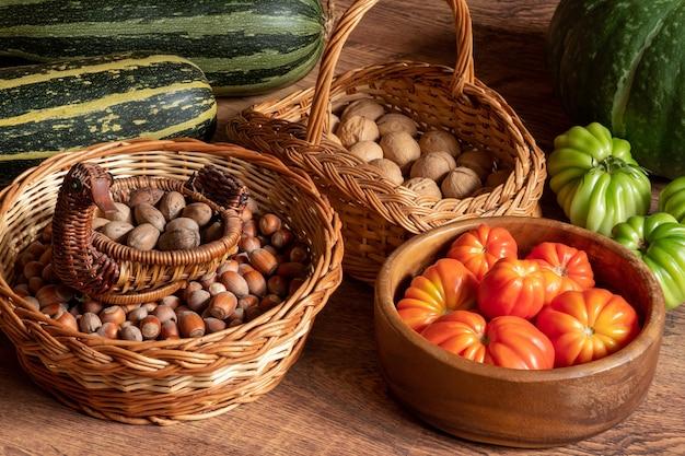 Abóbora de tomates e abobrinhas e cestos com avelãs e nozes empilhados no chão