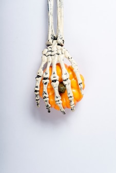 Abóbora de travamento do braço de esqueleto sobre o cinza.