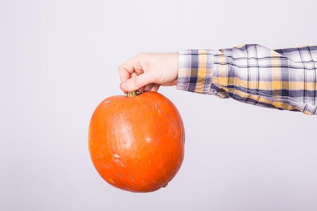 Abóbora do conceito de colheita e férias do outono na mão masculina no fundo branco