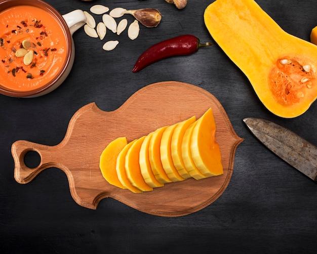 Abóbora é cortada em pedaços em uma tábua de cozinha