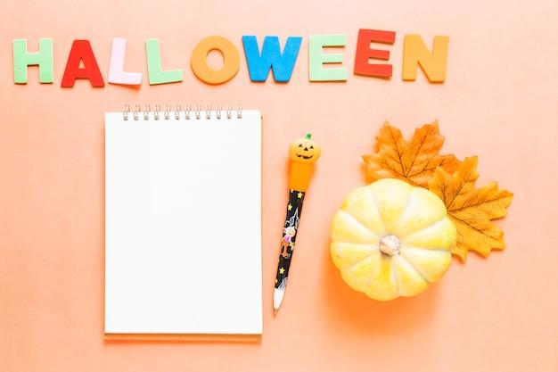 Abóbora e folhas perto de escrever e artigos de papelaria de halloween