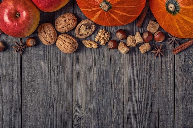 Abóbora e maçãs com nozes em uma mesa de madeira