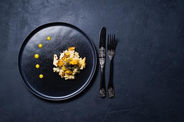 Abóbora e quinoa cozidos em uma placa preta. comida saudável vegan.