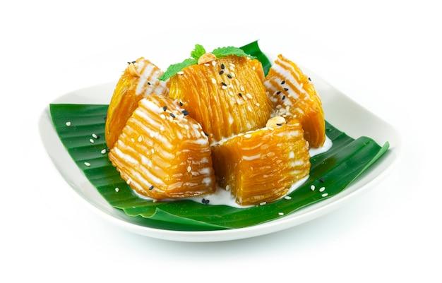 Abóbora em xarope coberta de leite de coco, amendoim e gergelim sobremesa tailandesa de prato de fusão vista lateral
