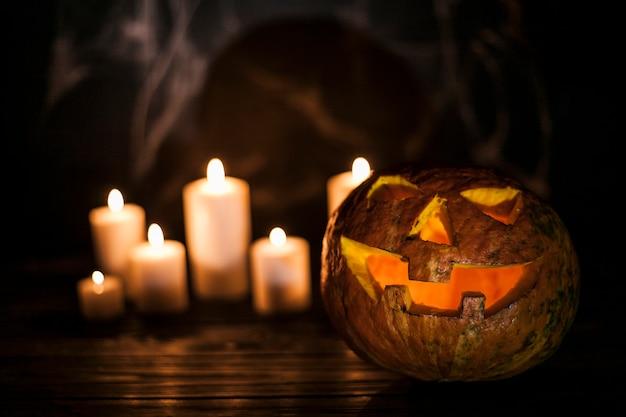 Abóbora esculpida assustador e velas brancas