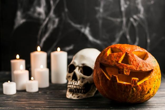 Abóbora esculpida e crânio humano com velas